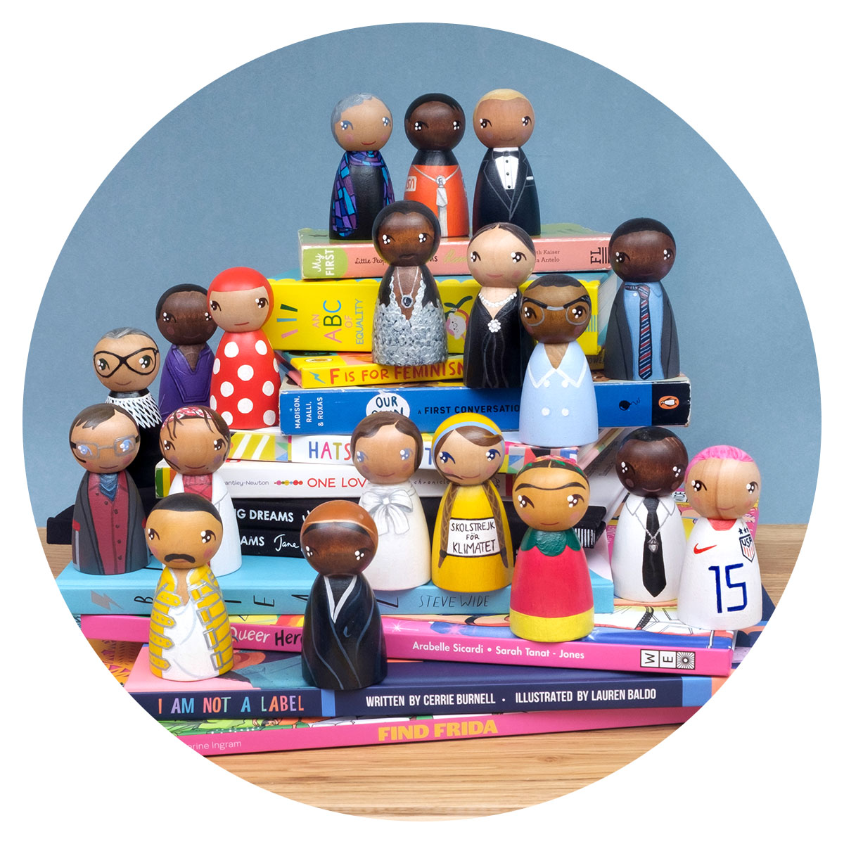Peggy Dollface wooden peg dolls painted by hand of inspirational people in history, sit on top of a pile of books